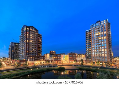 """View over water to typically residential apartments """"de Elementen"""" at night near the heemkanaal at the suburban Oosterheem, Zoetermeer, the Netherlands during dusk"""