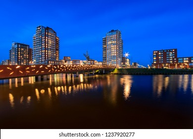 """View over water to typically residential apartments towers """"de Elementen"""" at night near the heemkanaal at the suburban Oosterheem, Zoetermeer, the Netherlands during dusk"""