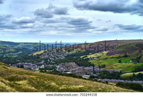 View over the Yorkshire town of Marsden, looking down from Marsden Moor showing historic mills, houses and the main roads towards Huddersfield from Olham and Manchester.