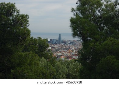 View overlooking Barcelona and the sea through greenery and trees