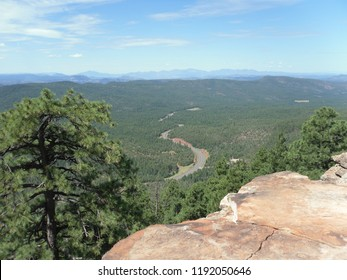 View overlooking the valley below the Mogollon rim. Foreground: rocky edge and some nearby trees. Background: Tonto National Forest, winding SR-260 highway, and distant mountains