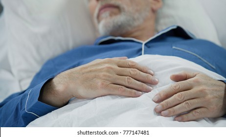 View of overworked wrinkled hands of wise old man peacefully drowsing in bed