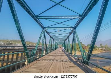 View of Pai Memorial Bridge orTha Pai World War II Memorial Bridge with tourist walking relax and blue sky background, Pai, Mae Hong Son, Thailand.