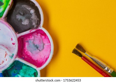 View of paint palette with different colors and paint brushes. Selective focus.