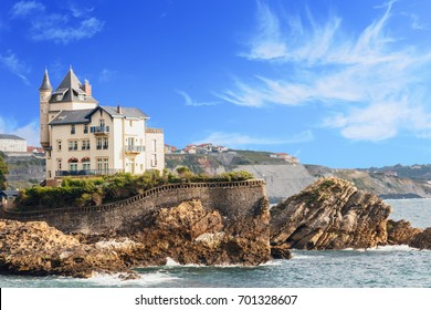 view of the Palace on the rocky beach against the blue sea and sky/view of the Palace on the rocky coast in the French city of Biarritz