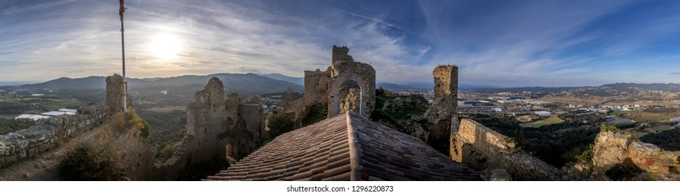 View of Palafolls castle medieval ruined stronghold between Girona and Barcelona on the Costa Brava with the Catalan flag proudly flying over the Romanesque church