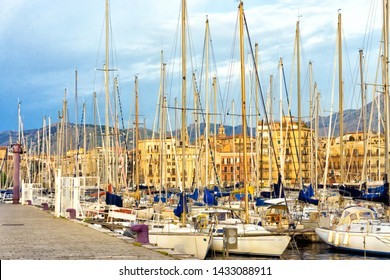 View of the Palermo port with boats and the city in the background in Sicily, Italy