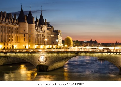 View of Paris by night with a bridge over the Seine river and the Conciergerie building near Notre-Dame