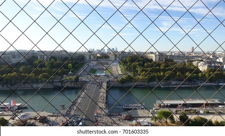 View of Paris from top of the Eiffel Tower through fence