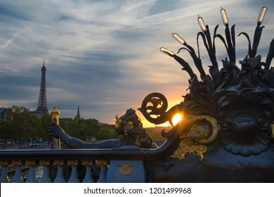 View from Paris's Alexander Bridge at sunset with the Eiffel Tower in the distance and a statue in the foreground
