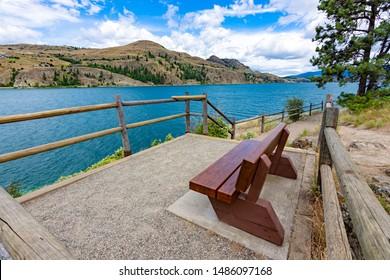 View of a park bench at Kalamalka Lake from Kalamalka Lake Provincial Park near Vernon British Columbia Canada on a summer day