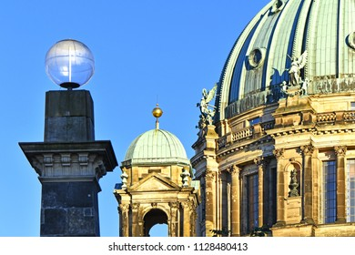 View to a part of the Berlin Dome in the downtown of Berlin in the evening sun. In the foreground you can see a pillar of the Friedrich`s Bridge with a great glass sphere.
