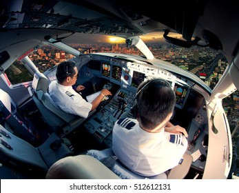 The view from the passenger aircraft cockpit. Pilots at work. The airplane climbs over the cityscape and skyscrapers at sunset.