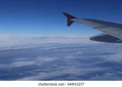 View from a passenger aircraft window flying above the clouds