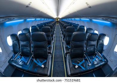 View of passenger seats in a blue-lit aircraft