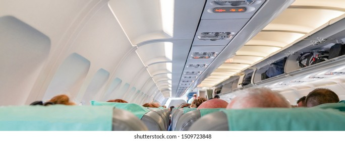 view of the passenger seats inside the airplane. passengers are sitting in the cabin. boarding people hand luggage