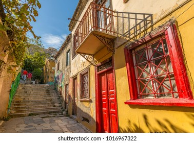 View of pastel coloured houses in Plaka District of Athens, overlooked by the Acropolis, Athens, Greece, Europe 12 October 2017