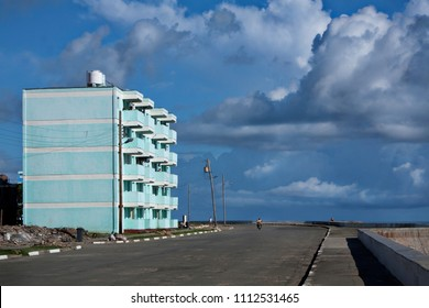 View of paved empty road with lonely biker riding by small residential house on seafront under blue sky in clouds, Cuba