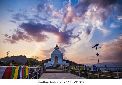 View of a peace pagoda, as a Shanti stupa, against the background of the sunset sky, in the neighborhood of the city of Pokhara, near the Lake Pheva in the Himalayas.