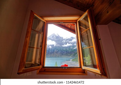 A view of peaceful Oeschinen Lake with majestic rocky mountains in background through the wooden window of a chalet house by the lakeside near Kandersteg, Bernese Highlands, Switzerland, Europe