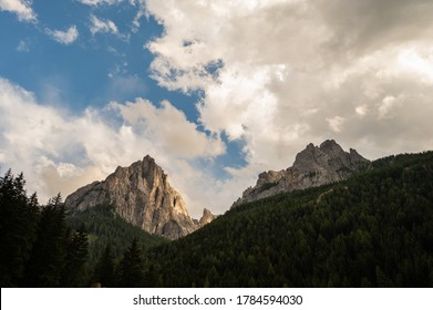 view of the peak of cima 11 and cima 12 inside Dolomites mountains surrounded by clouds seen by Pozza di Fassa village in Trento province, Italy