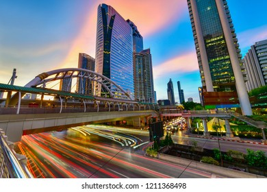 View of a pedestrian overpass in downtown of Bangkok City with high rise buildings in the background in evening light.