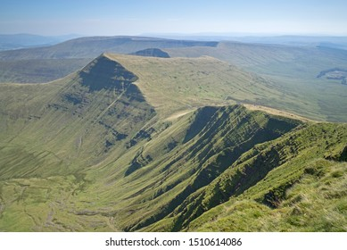 View from Pen Y Fan looking towards Cribyn, Brecon Beacons National Park, with sunlight shadow emphasising rock strata and escarpment face