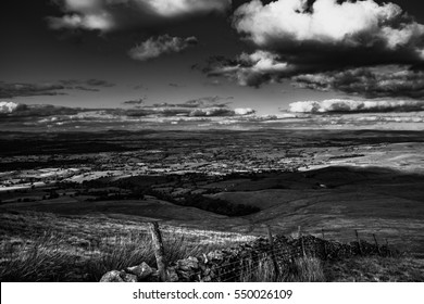 A view from Pendle Hill. Clouds cast shadows on Lancashire Hills. In distance Yorkshire Highest peaks: Pen-y-Ghent, Ingleborough, Whernside Lancashire, England, UK