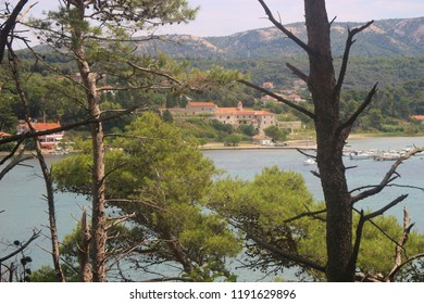 View from the peninsula and nature reserve Kalifront to the town Rab, Rab island, Croatia. The franciscan monastery St Anthony Abbot on the other side of the water strait. South-east Europe.