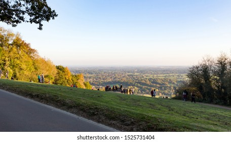 View of people enjoying and looking at the view of an autumn sunset from the top of Box Hill in Surrey