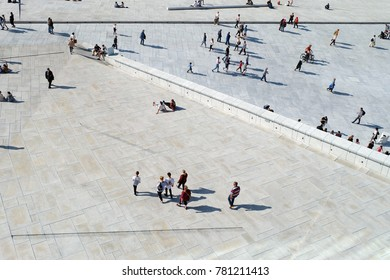 View of people enjoying the sun near Oslo Opera House (Operahuset) - the home of The Norwegian National Opera and Ballet, and the national opera theatre in Norway Oslo, Norway - 02/09/2017
