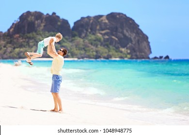 view of perfect tropical beach and father throwing his son high up and enjoying time together during vacation at fiji