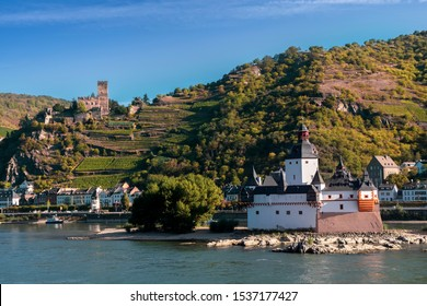 View of Pfalzgrafenstein Castle, known as the Pfalz, a famous toll castle on the Falkenau island and Gutenfels castle on the bank of the Rhine river, on a beautiful autumn day.