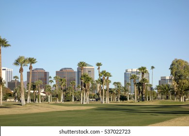 View at Phoenix Downtown from Encanto Park green lawns, Arizona; Copy space in clear blue sky