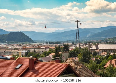 View of Piatra Neamt and the Batca Doamnei Lake with the cabla car passing over and Ceahlau mountain in the background.