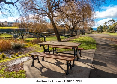 View of a picnic table by riverside footpath on a sunny winter day. Riverbank of Elizabeth River at Campbell Town. Tasmania