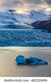 View of a piece of ice floating in the lake on the background of Vatnajokull glacier in evening