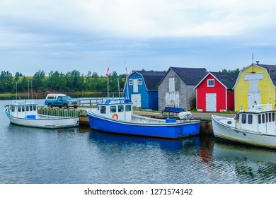 View of pier, fishing boats and colorful houses, in New London, Prince Edward Island, Canada