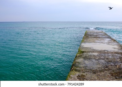 The view from the pier on the background of blue sea.