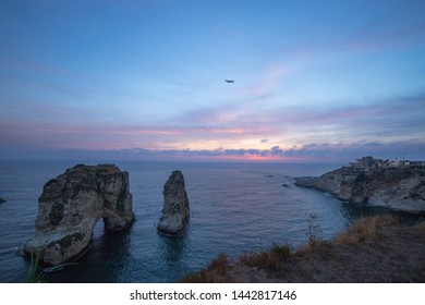 View of Pigeon Rock (Raouche) at sunset with an airplane flies over. Beirut, Lebanon