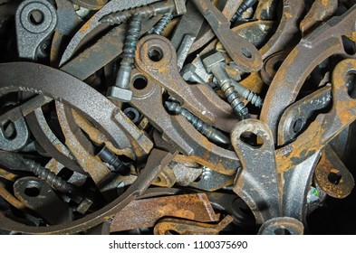 View of a pile of brackets and bolts quietly rusting in a bucket beside a civil engineering project.