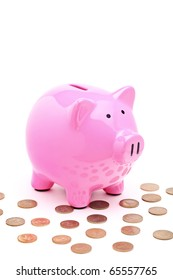 A view of a pink piggy bank and many coins isolated on white background