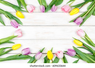 View pink and yellow tulips lying on a white wooden background