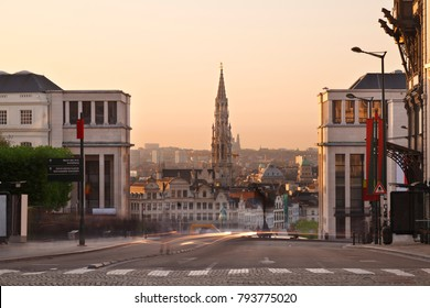 View from Place Royale to Grand Place with the tall tower of the Hotel De Ville. Long exposure shot with warm evening light.