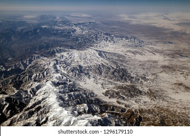 View from plane at clear day to hindu kush mountain range with snow at the summits