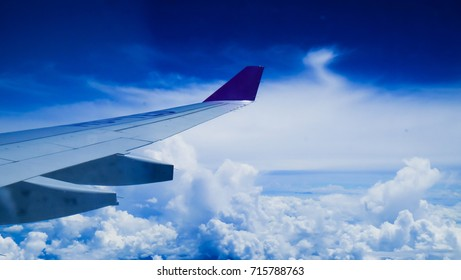 View of a plane window: a plane wing over clouds and blue sky.