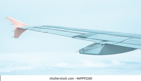 View of plane wing with cloud patterns blurred background.