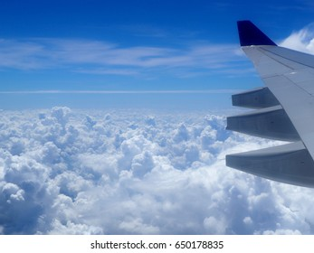 View of plane wing high over clouds in flight