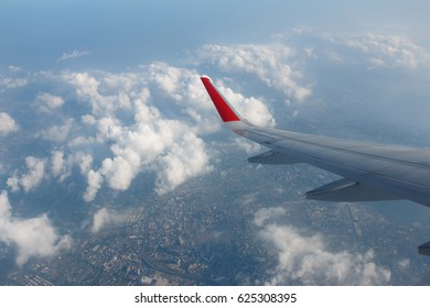 View of plane wing and sky from airplane window.