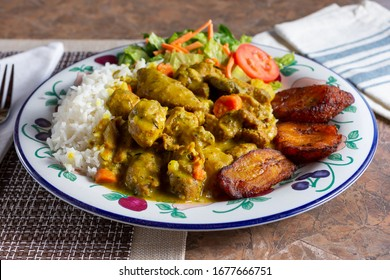 A view of a plate of curry chicken in a restaurant or kitchen setting.